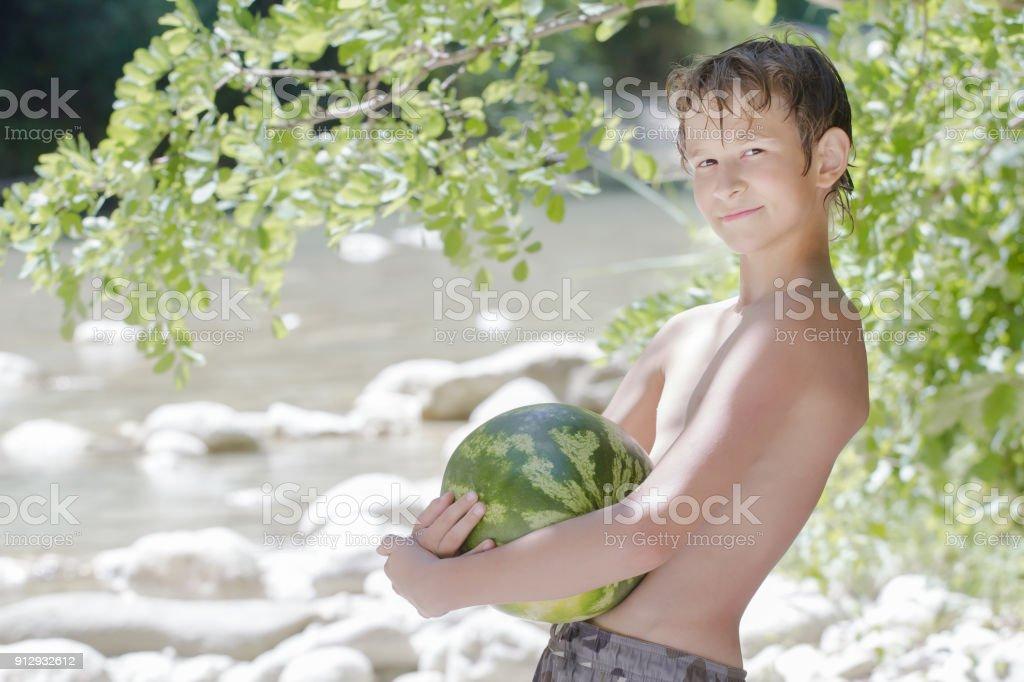 Boy in beach shade holding big green watermelon outdoors
