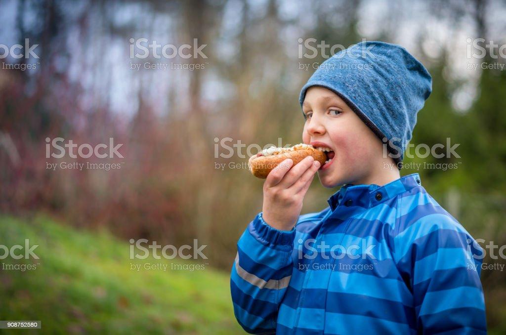 Boy in blue winter rain jacket and hat eating hotdog outdoors. stock photo