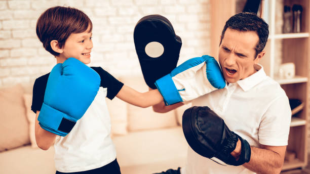 Boy in Boxing Gloves and Man Trainer in Apartment. stock photo