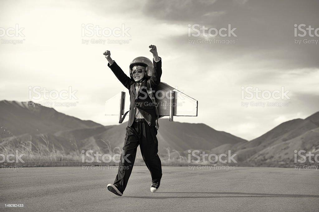 Niño en traje de negocios corriendo con cinturón cohete - foto de stock