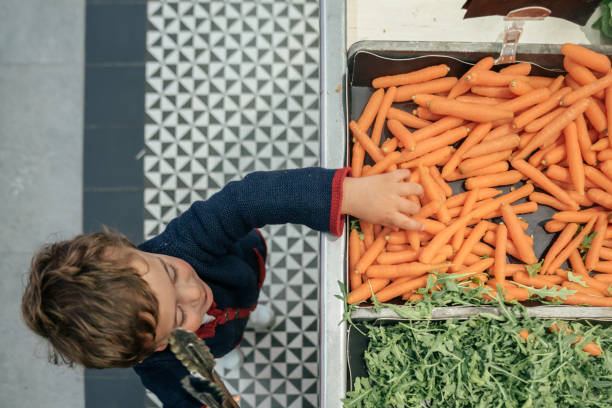 Junge bei der Wahl von Gemüse auf dem Markt – Foto