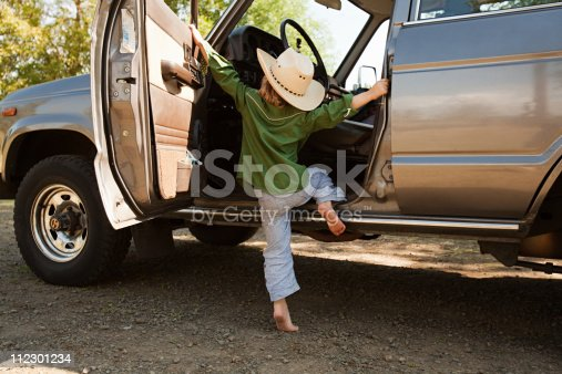 istock Boy in cowboy hat, climbing into station wagon 112301234