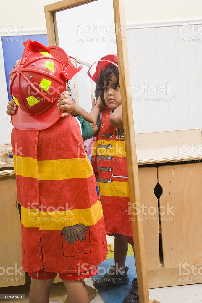 Boy in firefighter costume looking in full length mirror royalty-free stock photo