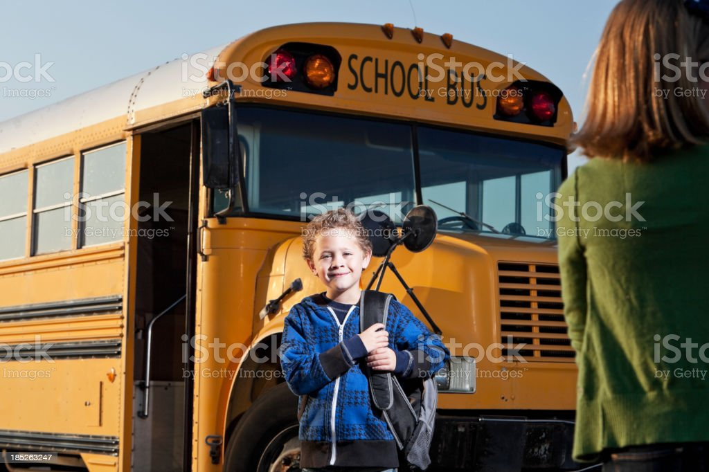 Boy in front of school bus stock photo