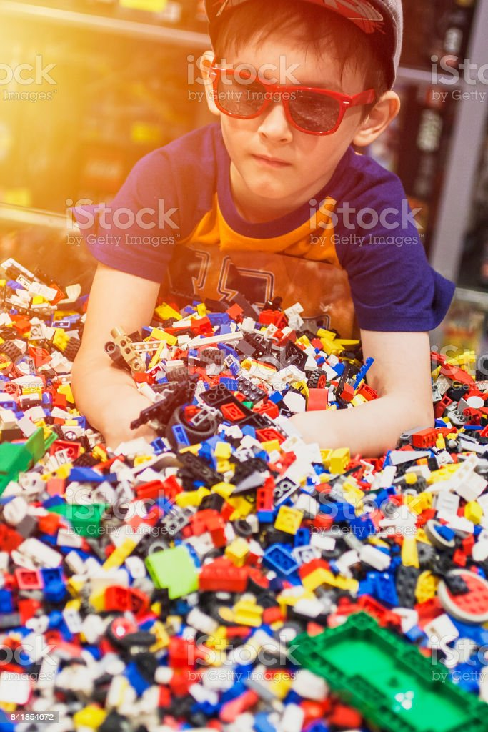 Boy in glasses play with many toys. stock photo