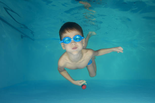 A boy in goggles plays underwater in a swimming pool stock photo