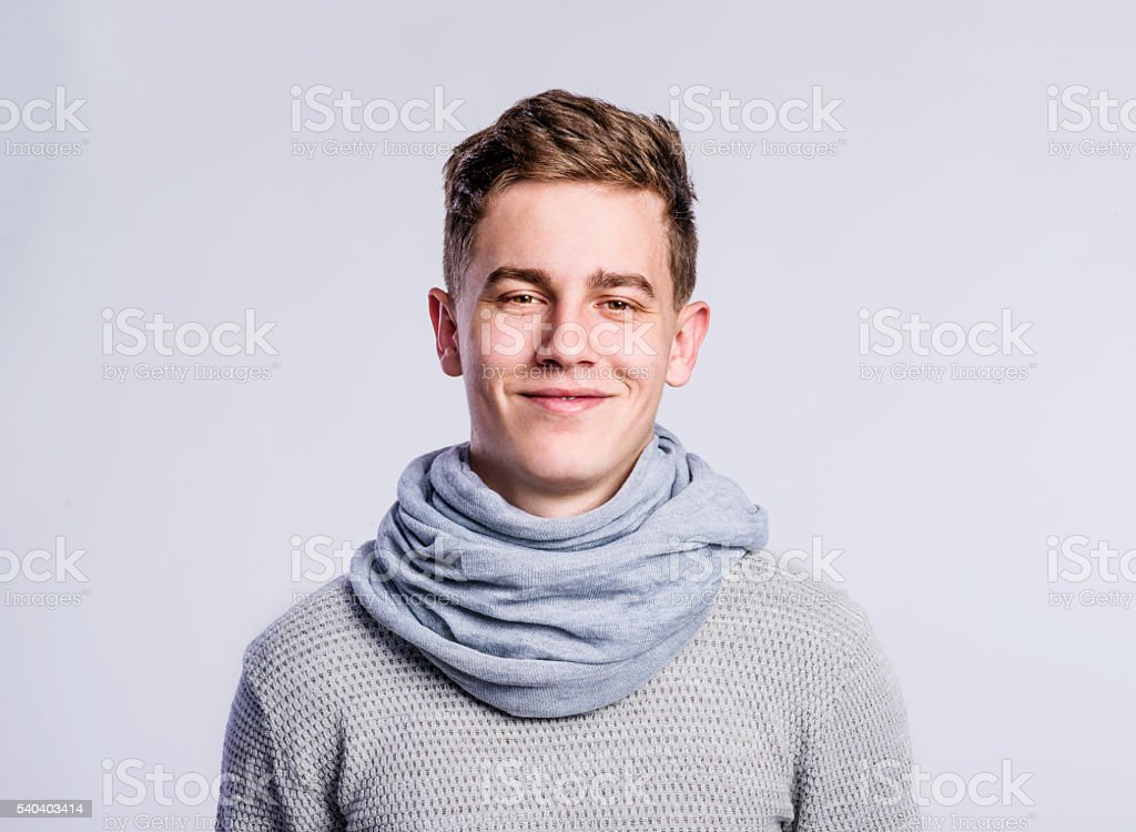 Boy in gray sweater and scarf, young man, studio shot stock photo