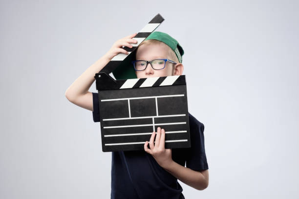 boy in green hat holding clapper board in hands. stock photo
