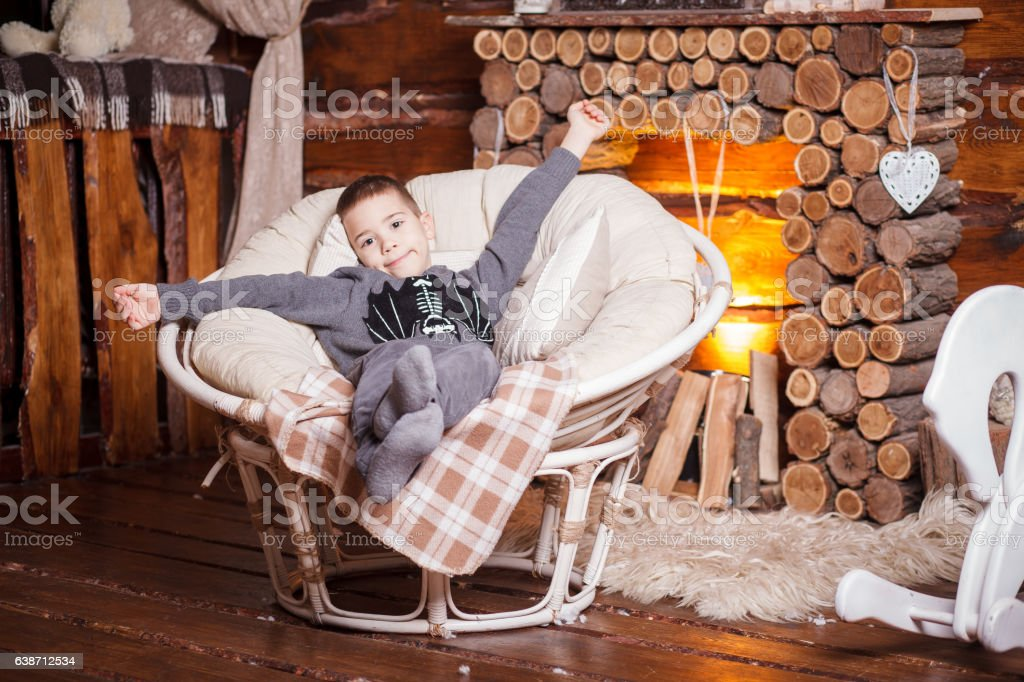 Boy in hat sitting in chair Christmas tree and gifts stock photo