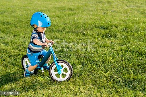 istock Boy in helmet riding a blue balance bike (run bike) 967318114