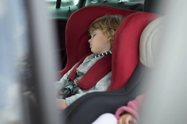 petit garçon dans un siège de sécurité pour enfant - child car sleep photos et images de collection