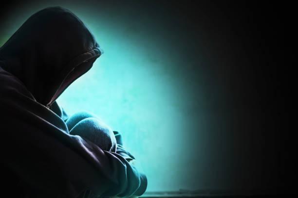 muchacho en campana con menor cabeza y brazo por estar de rodilla sentado en la esquina de la habitación en la oscuridad - human trafficking fotografías e imágenes de stock