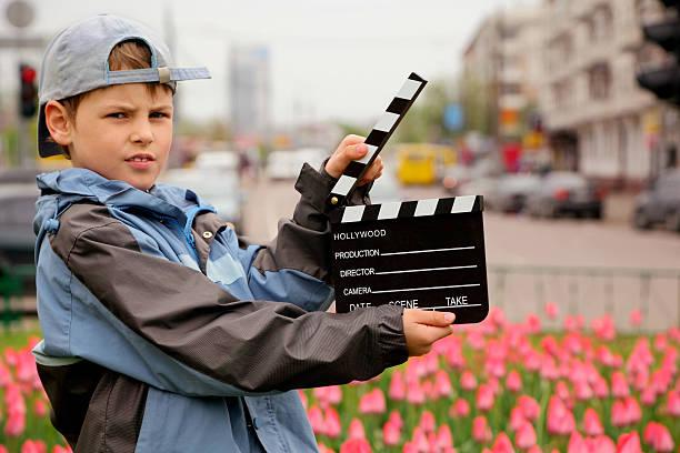 junge in jacke und eine mütze mit kino clapper board - klappe hut stock-fotos und bilder