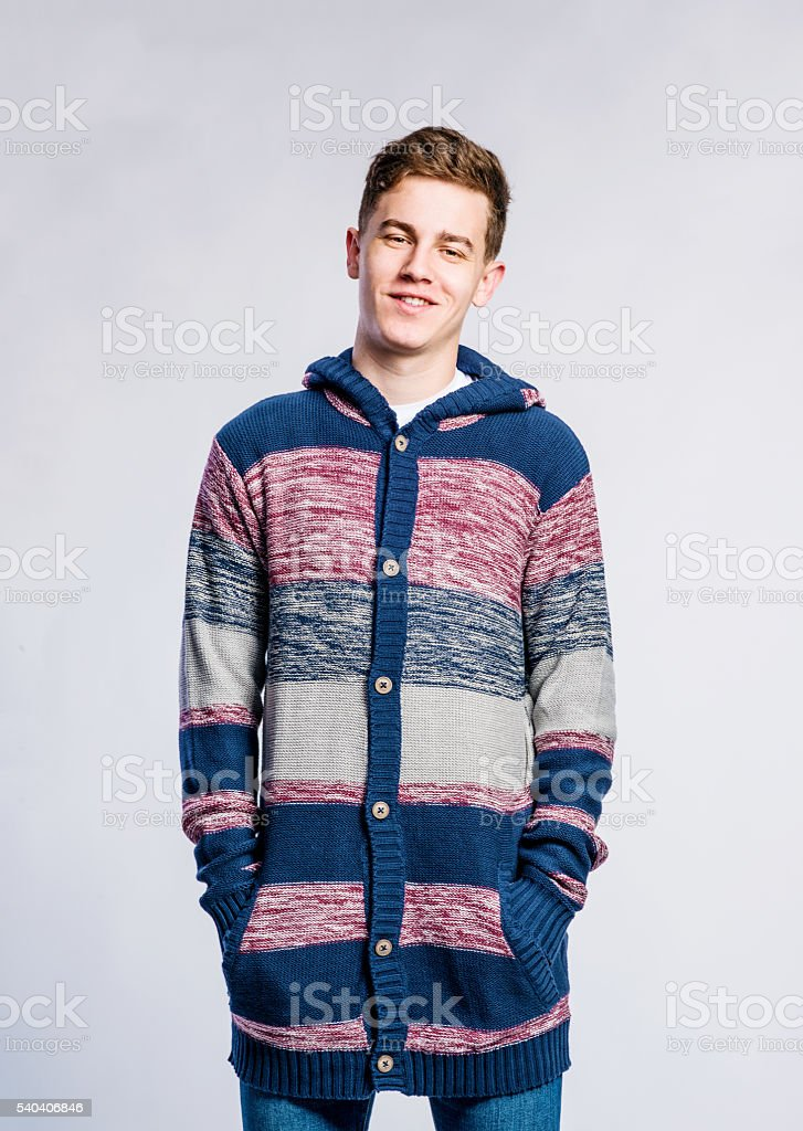 Boy in jeans and sweater, young man, studio shot stock photo