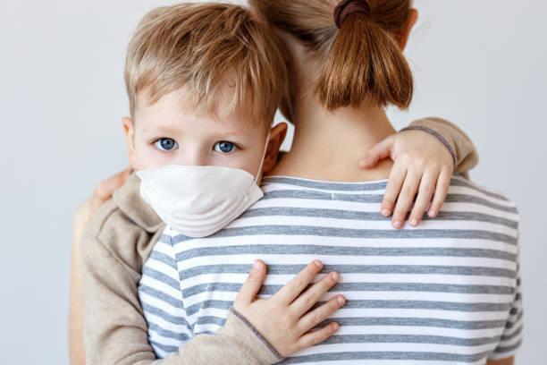 Junge in medizinischer Maske umarmt Mutter – Foto