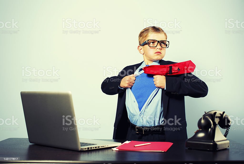 Boy in Office Dressed as Superhero at Laptop stock photo