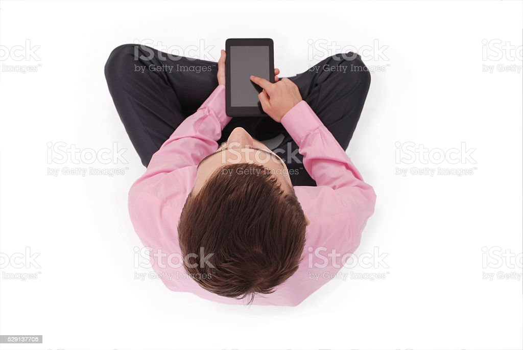 Boy in pink shirt sit and hold tablet PC stock photo