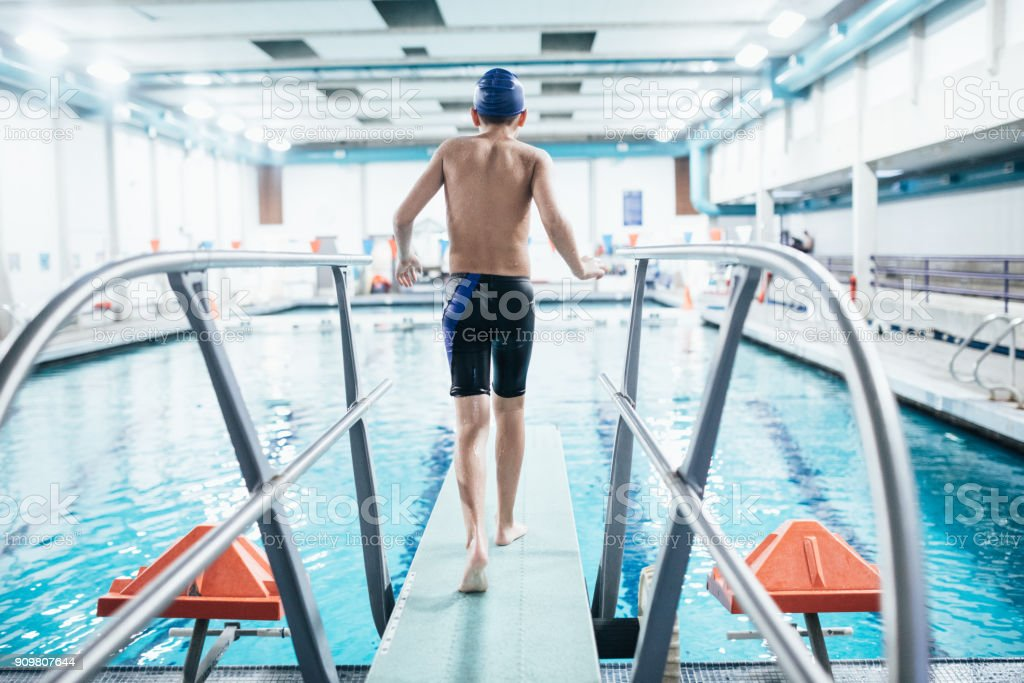 Boy In Pool on Diving Board stock photo