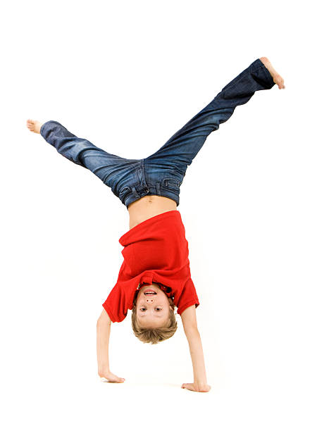 Boy in red shirt and jeans doing a handstand stock photo
