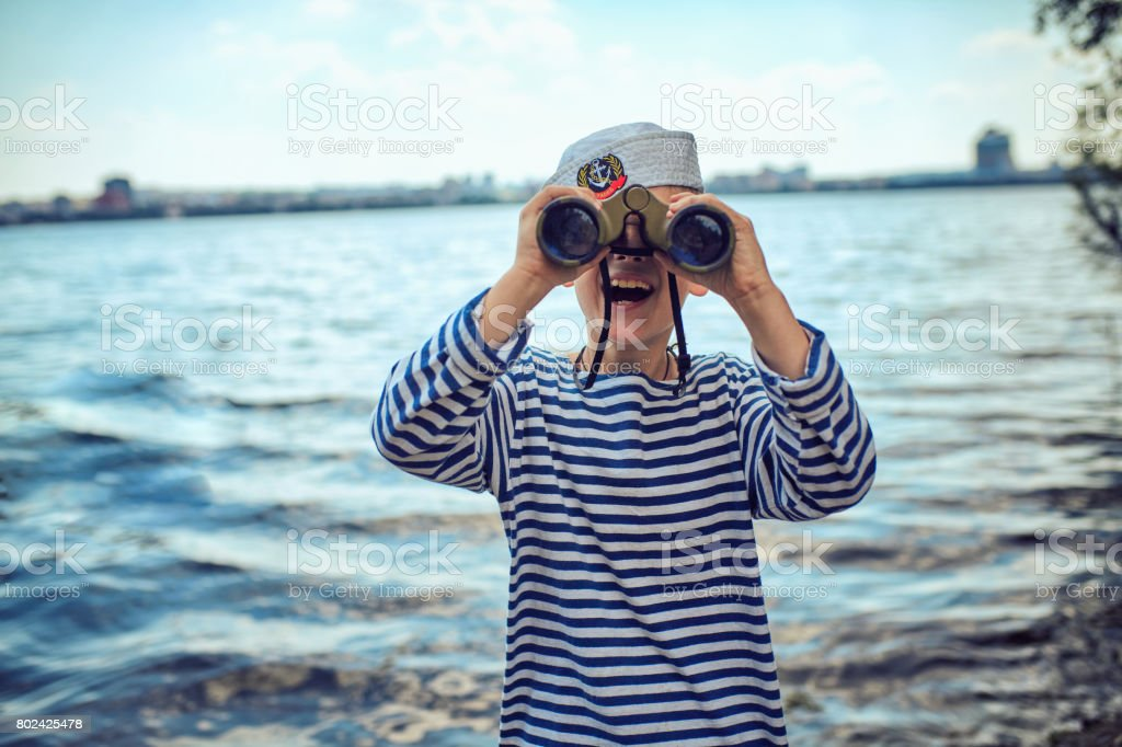 A boy in sailor's striped vest with binoculars stock photo