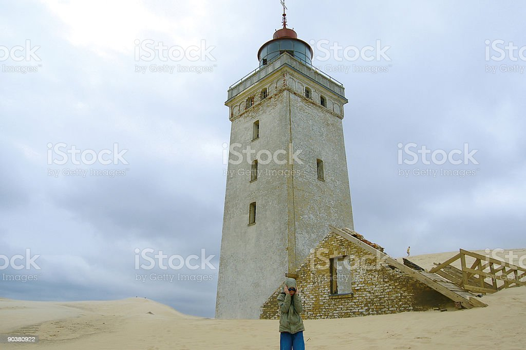 Boy in Sandstorm at Lighthouse stock photo