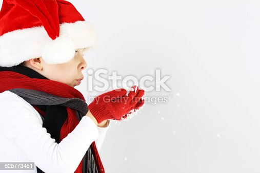 istock Boy in santa claus hat blowing snowflakes 525773451