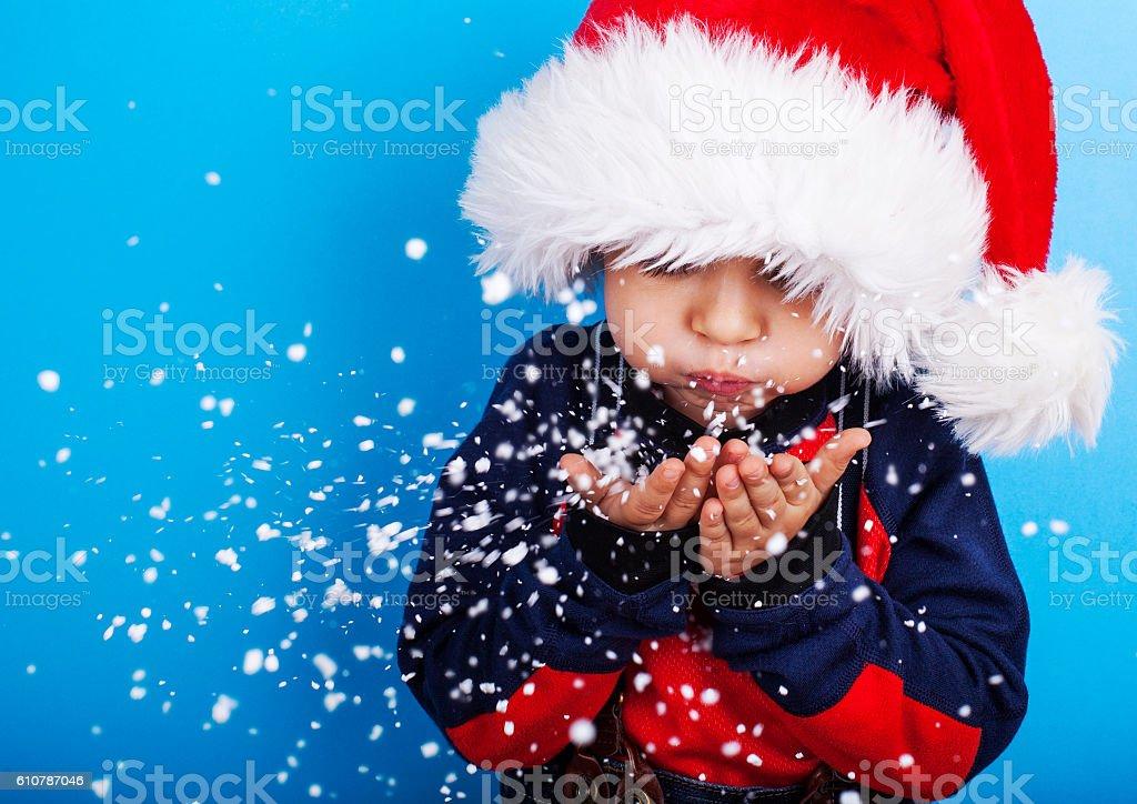 Boy in santa claus hat blowing snowflakes