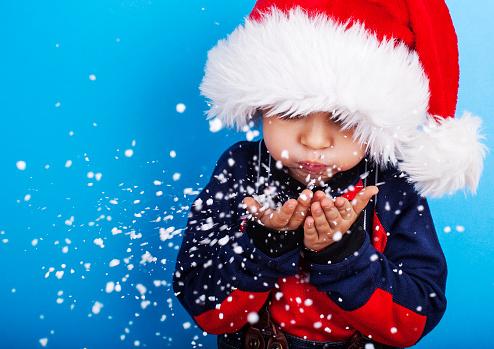 istock Boy in santa claus hat blowing snowflakes 610787046
