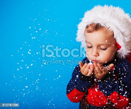 istock Boy in santa claus hat blowing snowflakes 610787090