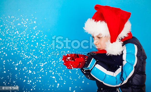 istock Boy in santa claus hat blowing snowflakes 610787948