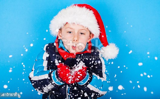 istock Boy in santa claus hat blowing snowflakes 610787974