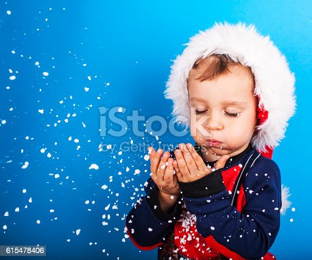 istock Boy in santa claus hat blowing snowflakes 615478406