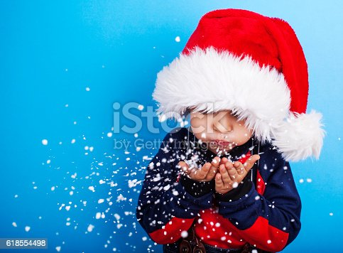 istock Boy in santa claus hat blowing snowflakes 618554498