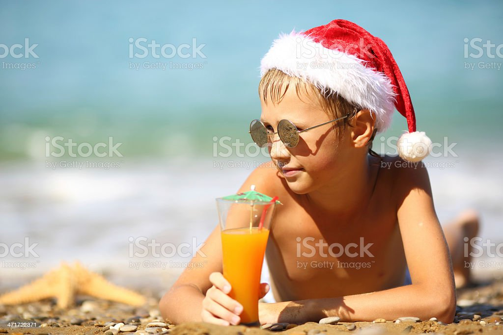 boy in Santa Claus hat on the beach royalty-free stock photo