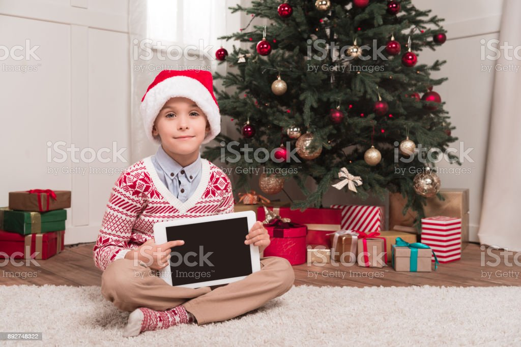 boy in santa hat holding tablet stock photo