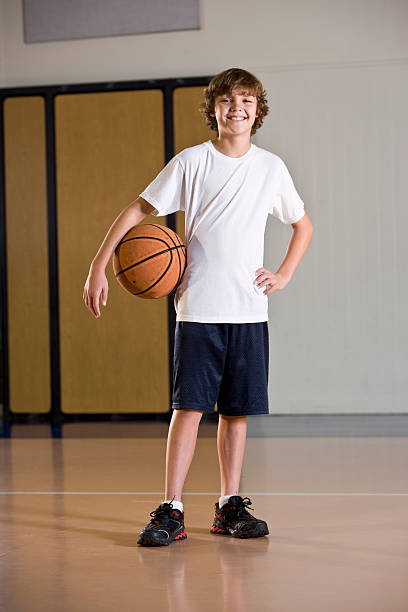 Boy in school gym holding basketball stock photo
