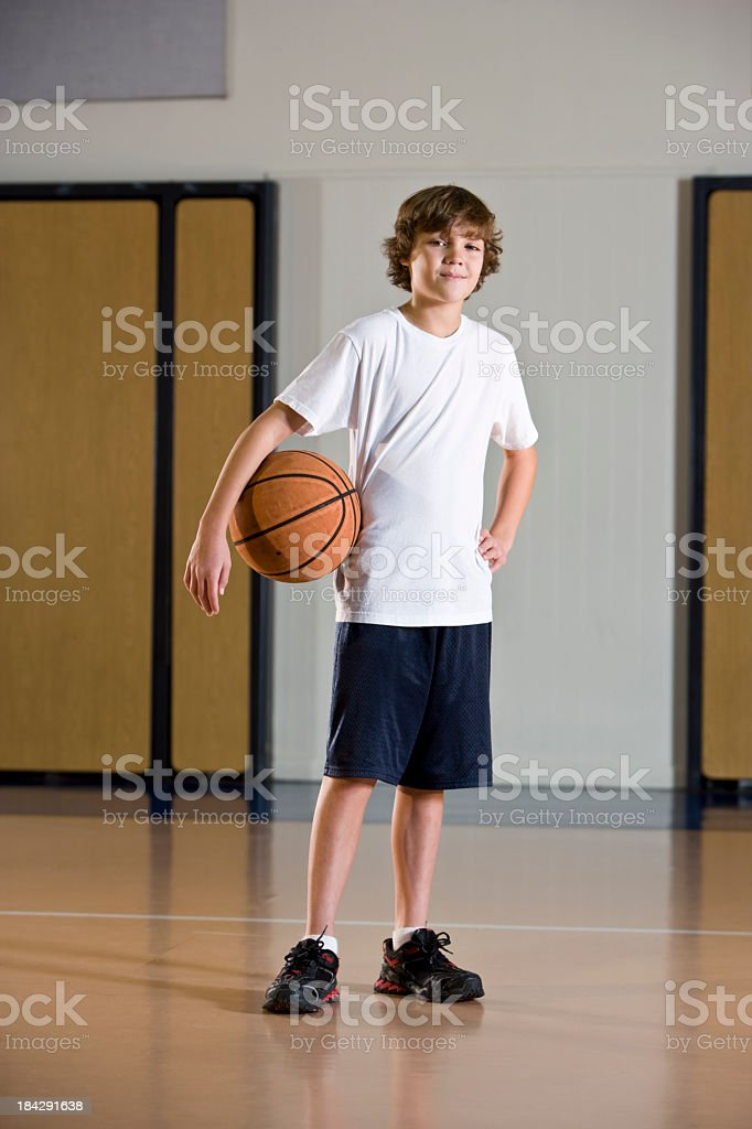 Boy, 9 to 10 years, in gym playing ball.