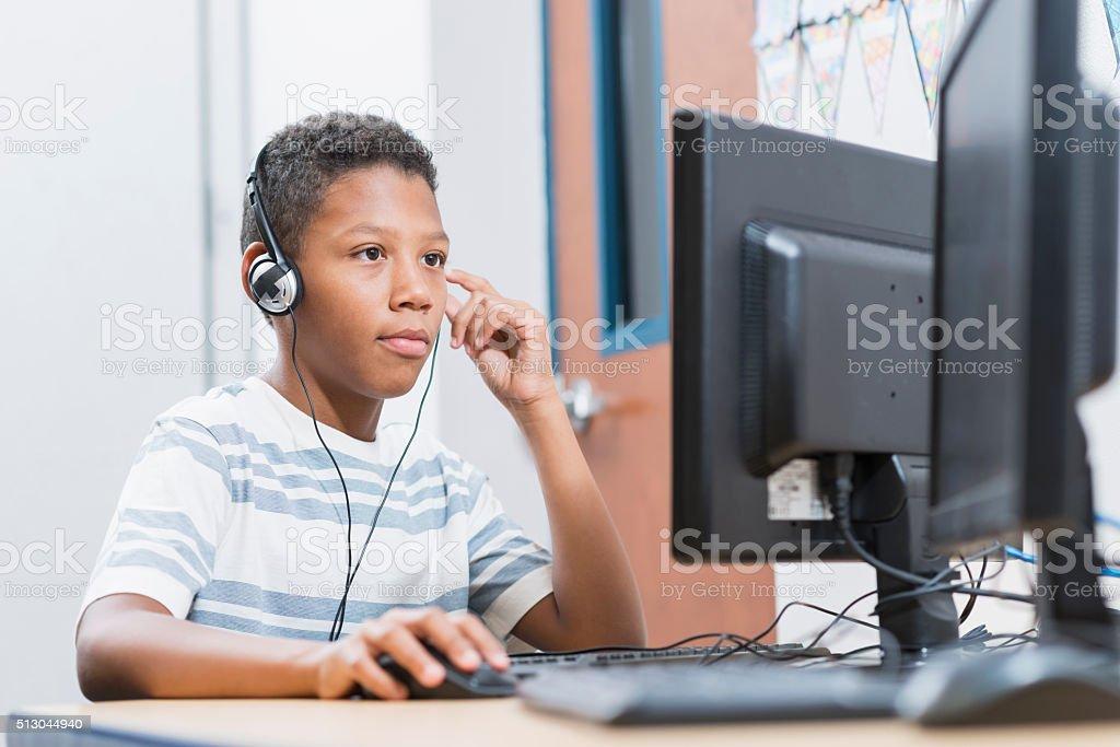 Boy in school using desktop computer wearing headphones stock photo
