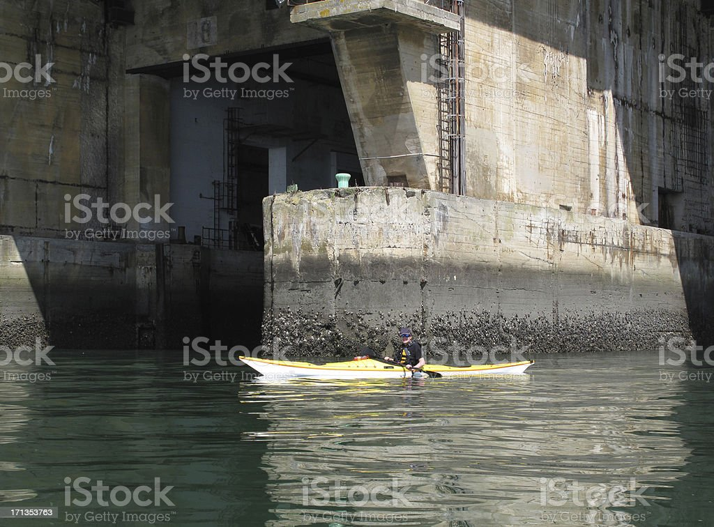 Boy in sea kayak at u-Boat Pens, Lorient, France stock photo