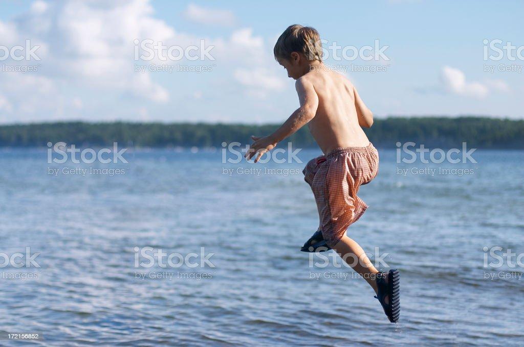 Boy in shorts jumping mid-air into lake stock photo
