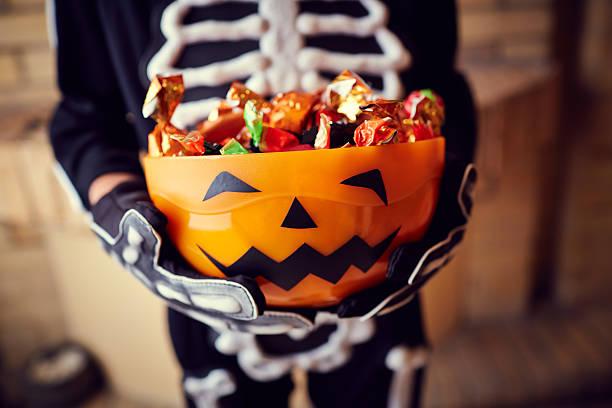 ragazzo in costume scheletro che tiene la ciotola piena di caramelle - halloween foto e immagini stock