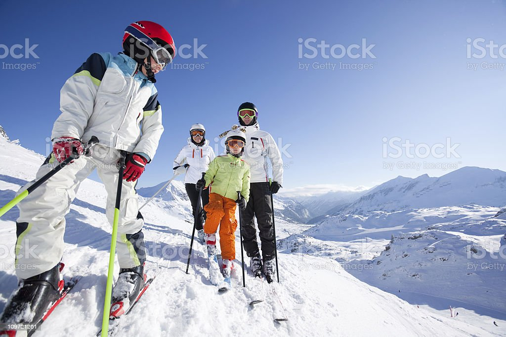boy in skiing outfit with his family royalty-free stock photo