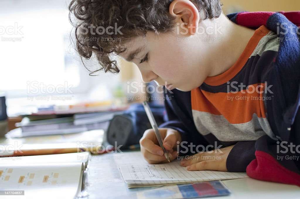 Boy in striped shirt doing homework royalty-free stock photo