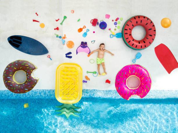 boy in swimming pool surrounded with toys - brinquedos na piscina imagens e fotografias de stock