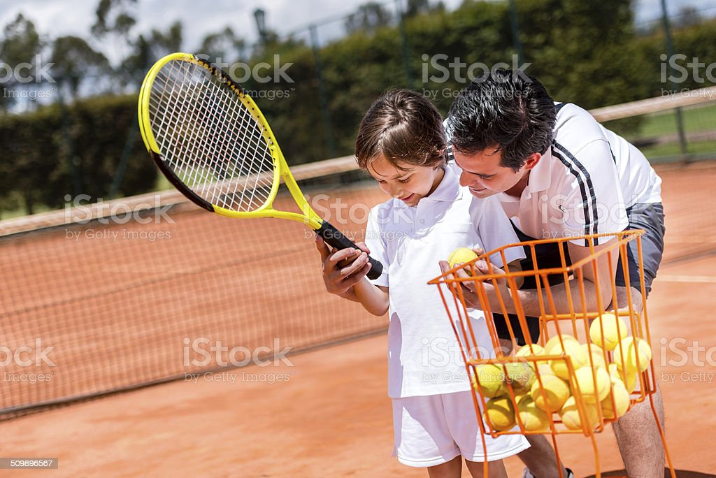 Boy in tennis lessons stock photo
