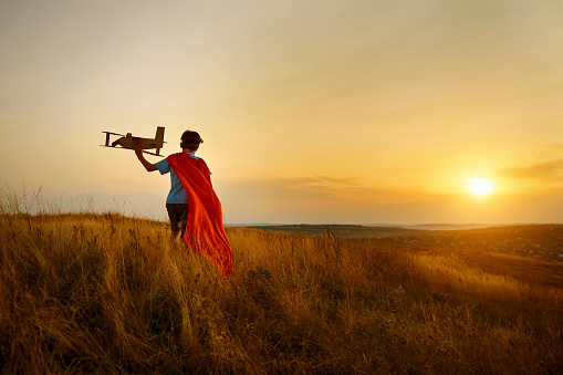 istock A boy in the costume of  pilot walking on the field at sunset. 845070732