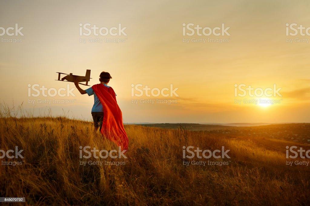 Un niño en el traje de piloto para caminar en el campo al atardecer. - foto de stock