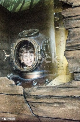 Little boy looking from inside the helmet of an old diving suit.