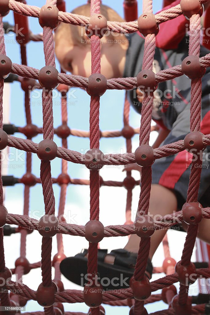 Boy in the net on playground royalty-free stock photo