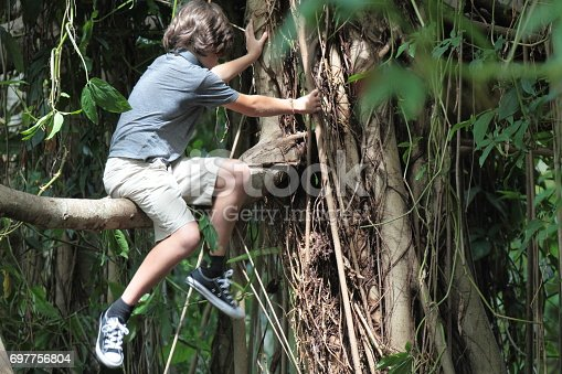 istock Boy in the tropical rainforest is sitting on a tree brunch. 697756804